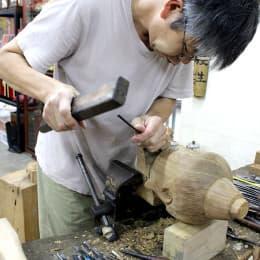 「大昌佛像雕刻木器」負責人 曾德衡展示木雕佛像模型的頭部。