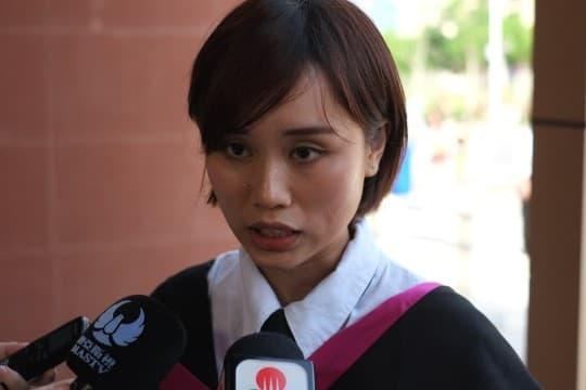 在澳大畢業典禮會場上舉標語的杜小姐認為校方做法粗暴。