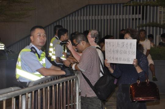 有香港市民舉牌希望警察別為選委效力,但警察沒有理會。