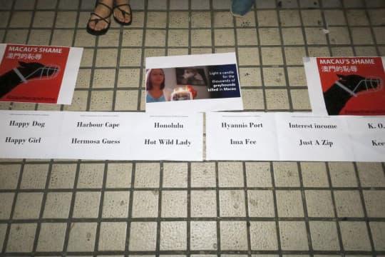 地上放置標語,以及寫有被殺狗隻名字的海報。
