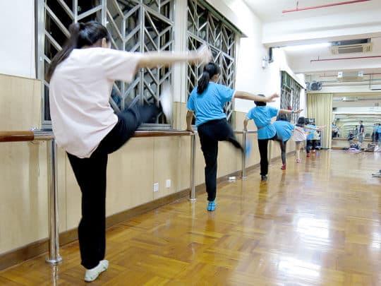 女學員們靠在扶手上練習踢腿。