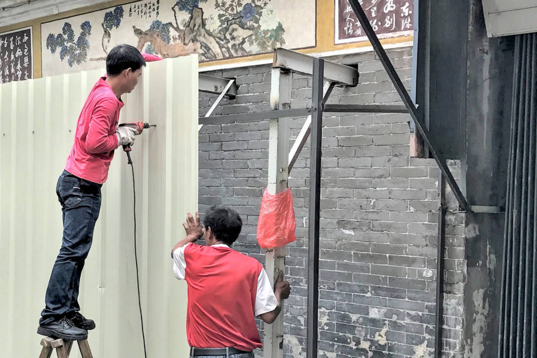工人於蓮溪廟外牆架起支撐架。