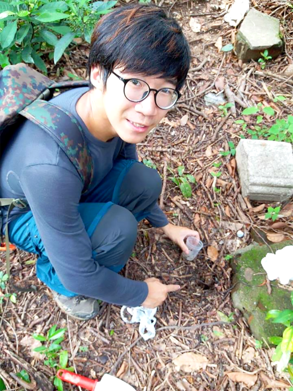 昆蟲學者梁志文在青州山上採集標本。