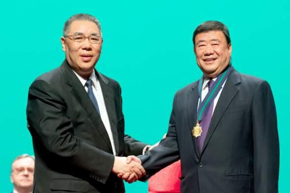 前任行政長官崔世安(左)向澳門科技大學校監廖澤雲頒授金蓮榮譽勳章。