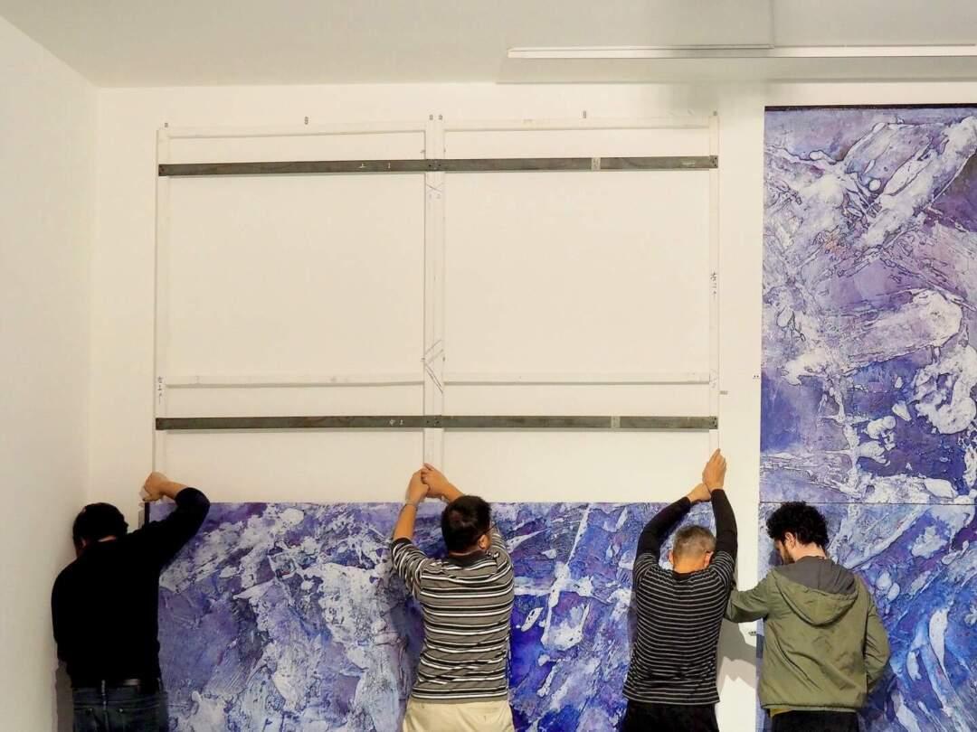 《爭衡圖》威尼斯展場組裝情況。山中理繪表示,佈展時這是令人最頭痛的作品之一。「因為這張畫很大,威尼斯那邊的牆比較軟。所以佈展組的同事造了一個可以借地下的力、承載得到這畫的畫框,裝了上去後再裝畫。當時特地找了兩個當地的技術人員一起幫忙,要差不多五六個人一起上。那裡就花了點時間。」相片由藝博館提供